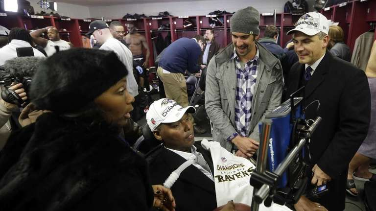 Former Baltimore Ravens player O.J. Brigance, center, his