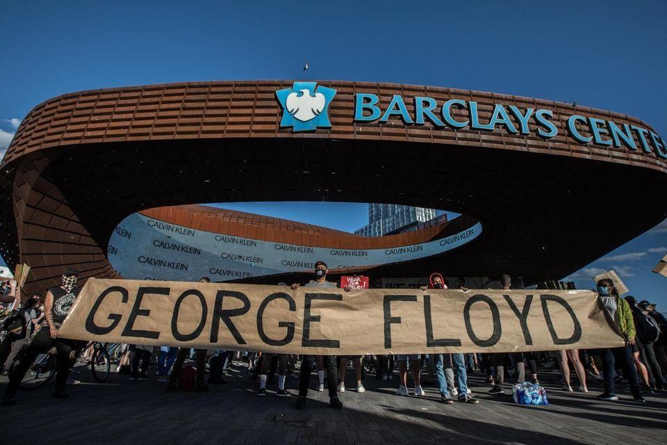 "A sign reading ""George Floyd,"" a black American"