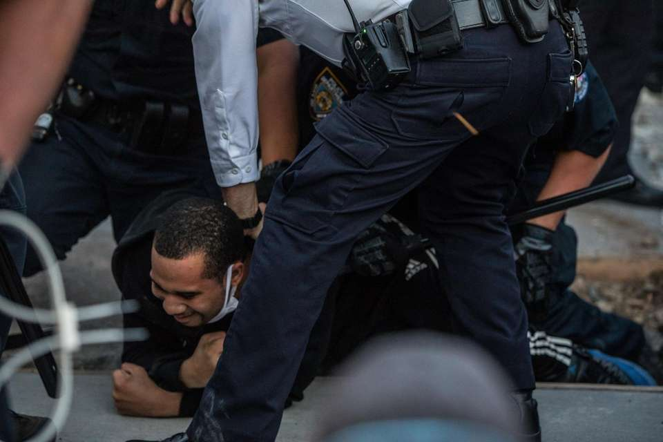 A man is detained during continuing protests stemming