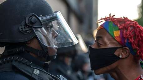 A protester confronts police during a rally in