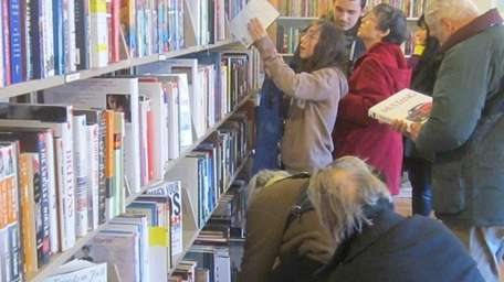 Customers look through books at the grand reopening