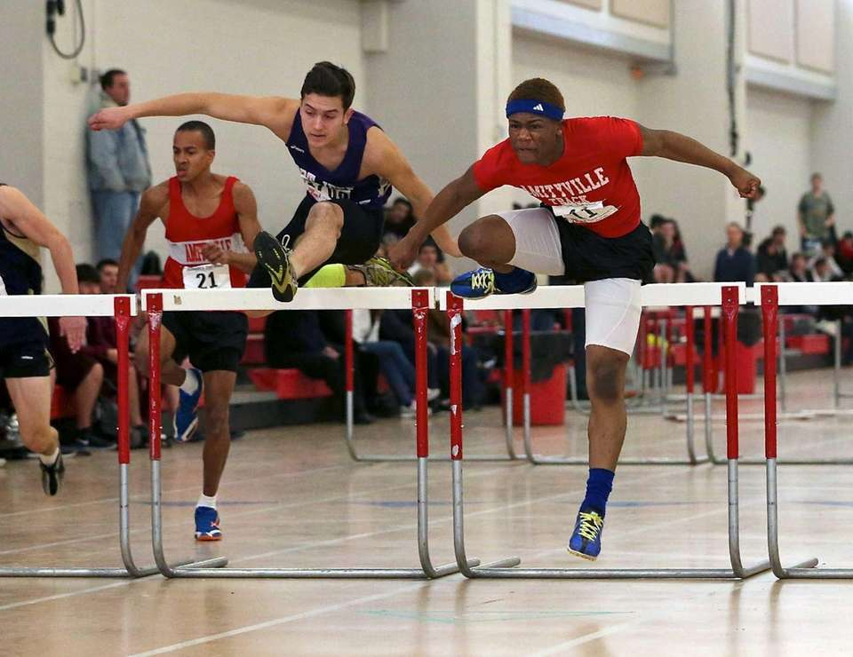 Amityville's O'Neil Armstrong, right, clears the last hurdle
