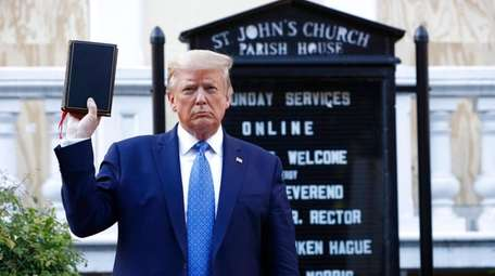 President Donald Trump holds a Bible on Monday