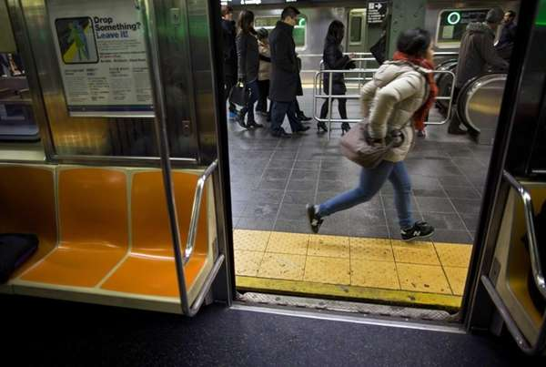 Passengers move near a train doorway on the