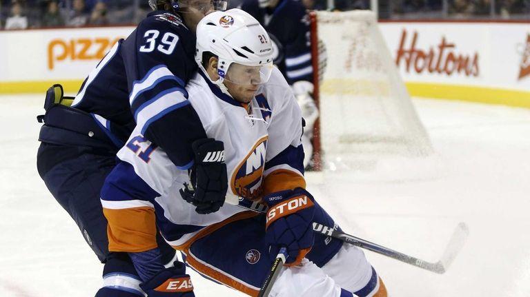 Winnipeg Jets' Tobias Enstrom and Islanders' Kyle Okposo