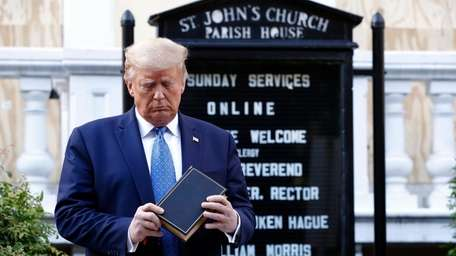 President Donald Trump holds a Bible during a