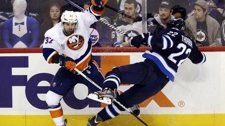 Islanders' Brian Strait checks Winnipeg Jets' Chris Thorburn