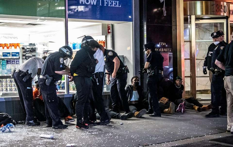 Police officers surround a group of people suspected