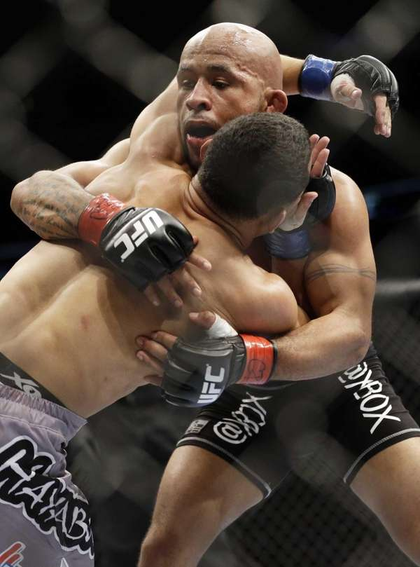 Demetrious Johnson, right, fights John Dodson during UFC