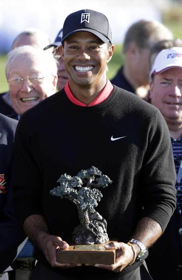 Tiger Woods poses with the trophy after winning