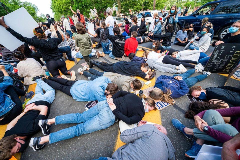 Protestors in Bridgehampton lie in the road, with