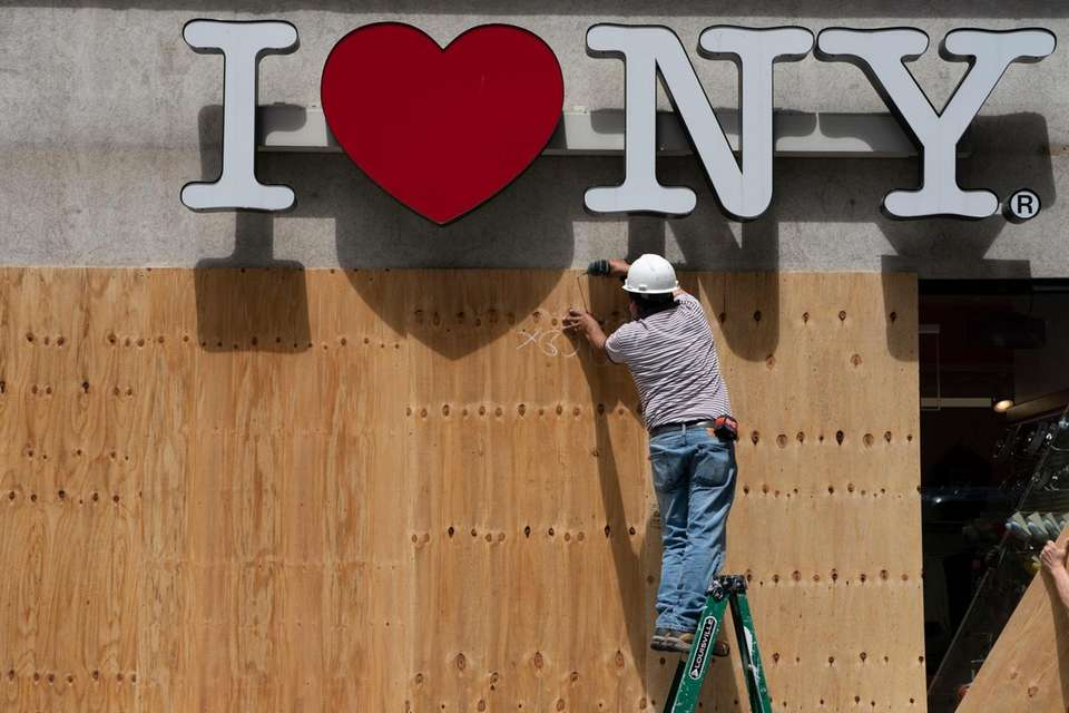 Workers board up a store in lower Manhattan