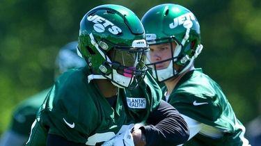 Jets quarterback Sam Darnold hands off to running