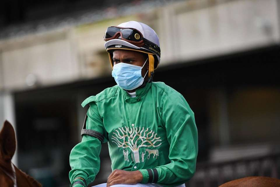 Jockeys ride out on their horses during the