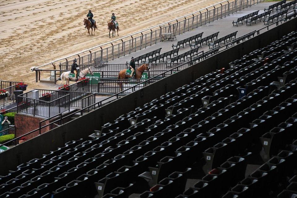 Horses run the track in an empty stadium