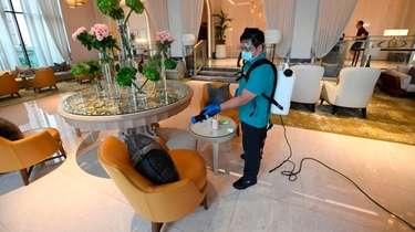 A mask-and-glove-clad cleaning staff member of the Jumeirah