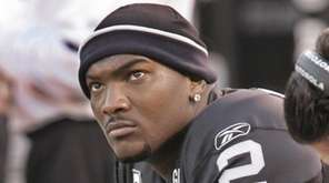 Oakland Raiders quarterback JaMarcus Russell sits on the