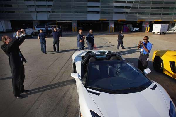 Airport workers look at the new Lamborghini Aventador