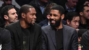 Kyrie Irving, right, chats with teammate Kevin Durant