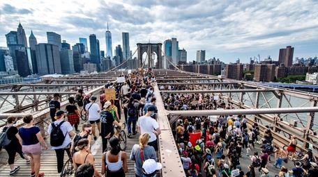 Protesters walk on the Brooklyn Bridge toward Manhattan