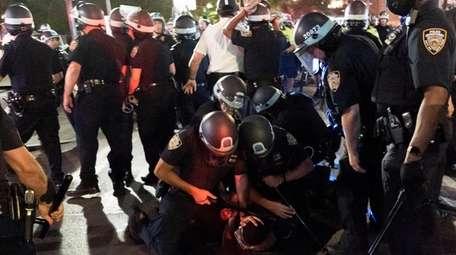NYPD officers detain a demonstrator late Thursday night