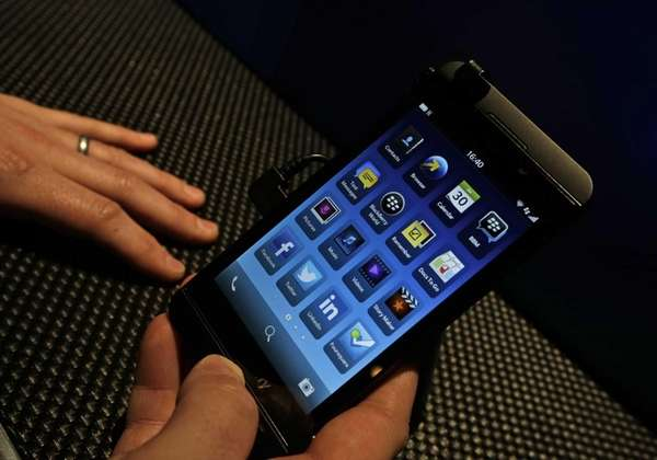 A man holds the new touchscreen BlackBerry Z10