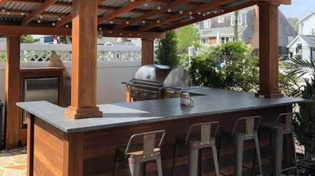This Babylon home has an outdoor kitchen designed