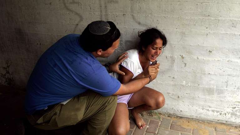 An Israeli girl reacts after a rocket fired