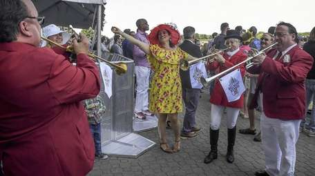 A woman dances to the buglers at Belmont