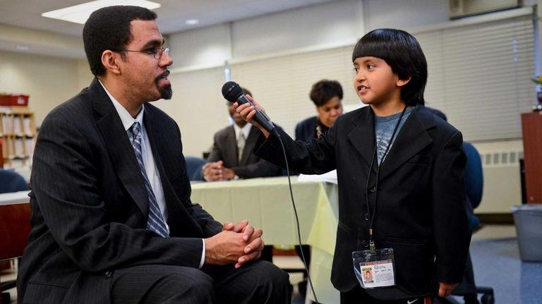Commissioner John B. King Jr., left, is interviewed