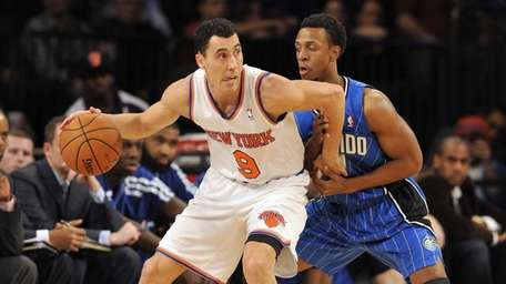Pablo Prigioni is closely guarded by the Orlando