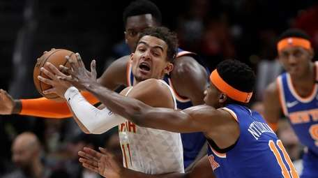 Atlanta Hawks guard Trae Young is covered by