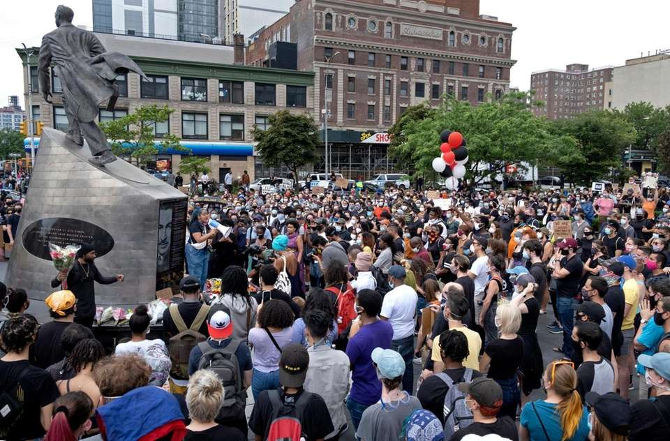 People attend a vigil in Harlem Friday, June