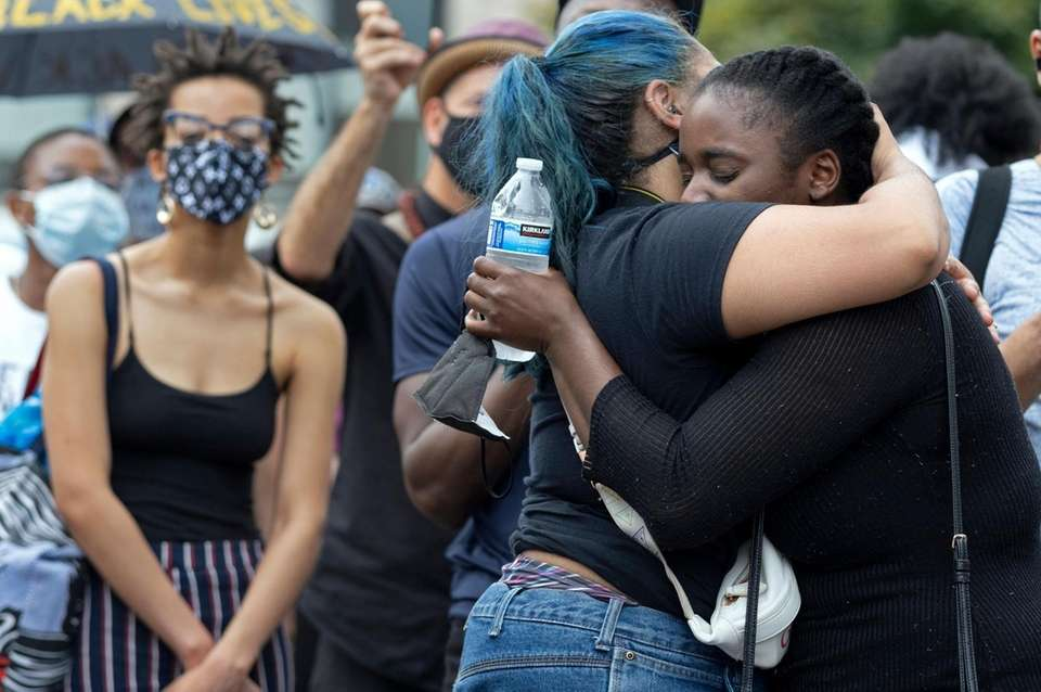 People embrace at a vigil in Harlem Friday,
