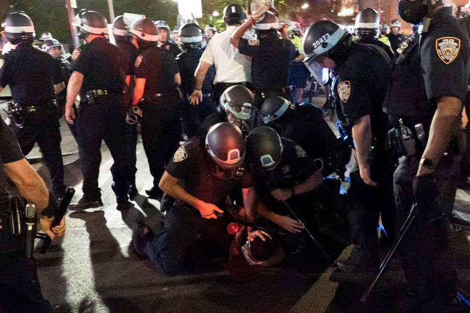 NYPD officers detain demonstrators who are protesting over