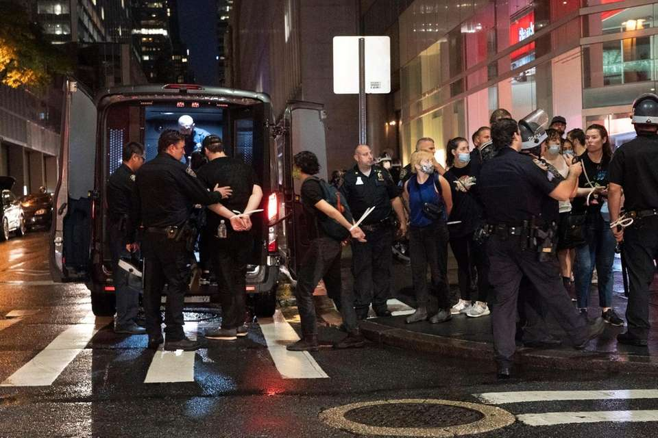 Members of the NYPD arrest demonstrators who continued