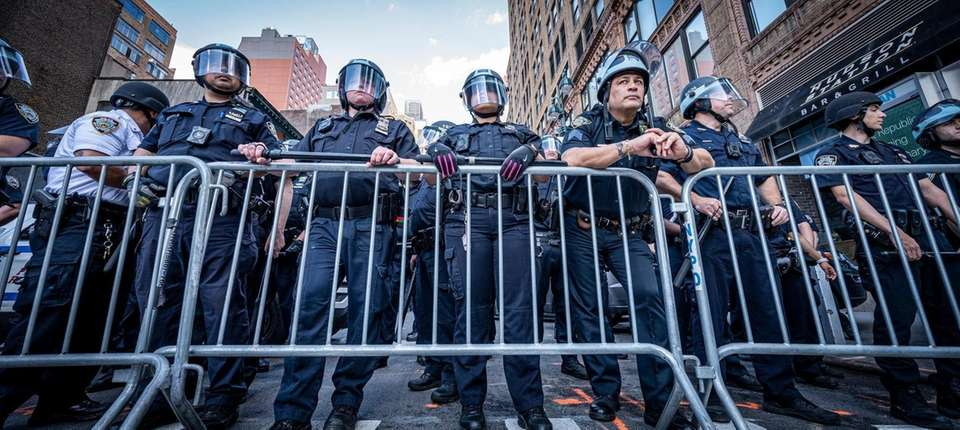 Protesters face the NYPD, while they rally through