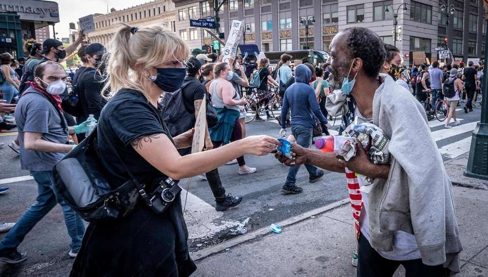 Protesters stop to give a homeless man money
