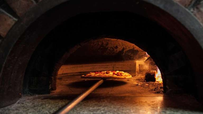 The pizza picante emerges from the oven at