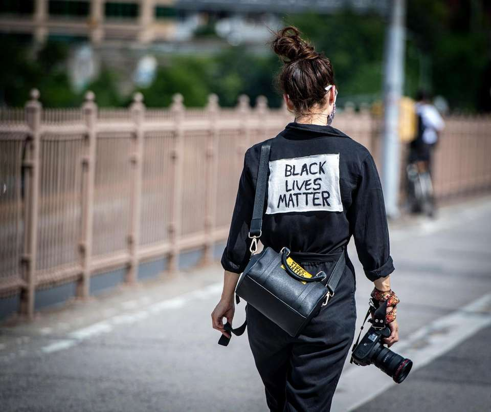 A woman walking with a camera voices her