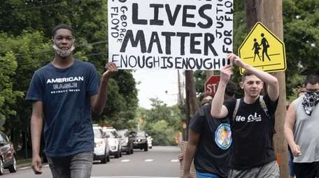 Protesters march Sunday from the Rosyln LIRR train