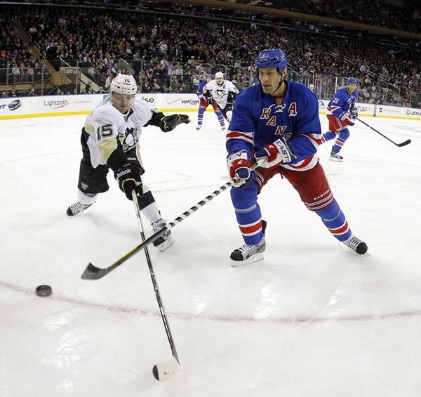 Dan Girardi clears the puck from Dustin Jeffrey