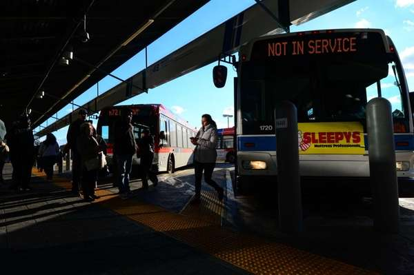 Commuters wait to board NICE buses at The
