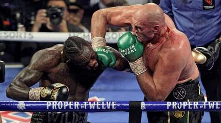 Tyson Fury (R) slams a right to the
