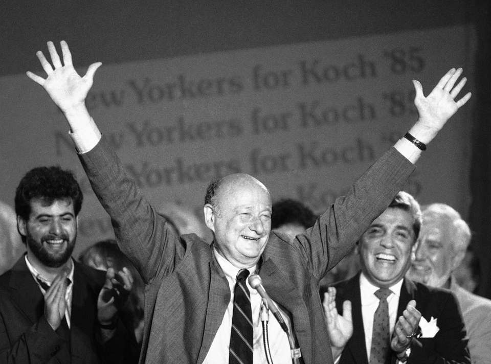 New York Mayor Ed Koch raises his arms