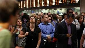 Passengers crowd Penn Station as they look up