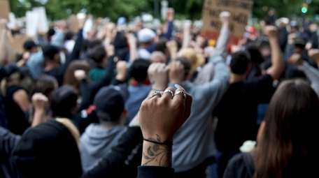 A demonstrator holds up a fist in Portland,