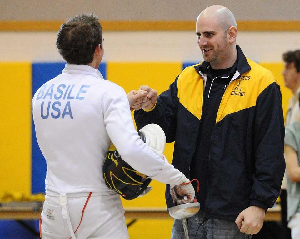 Jericho fencing head coach Seth Skolnick, right, congratulates