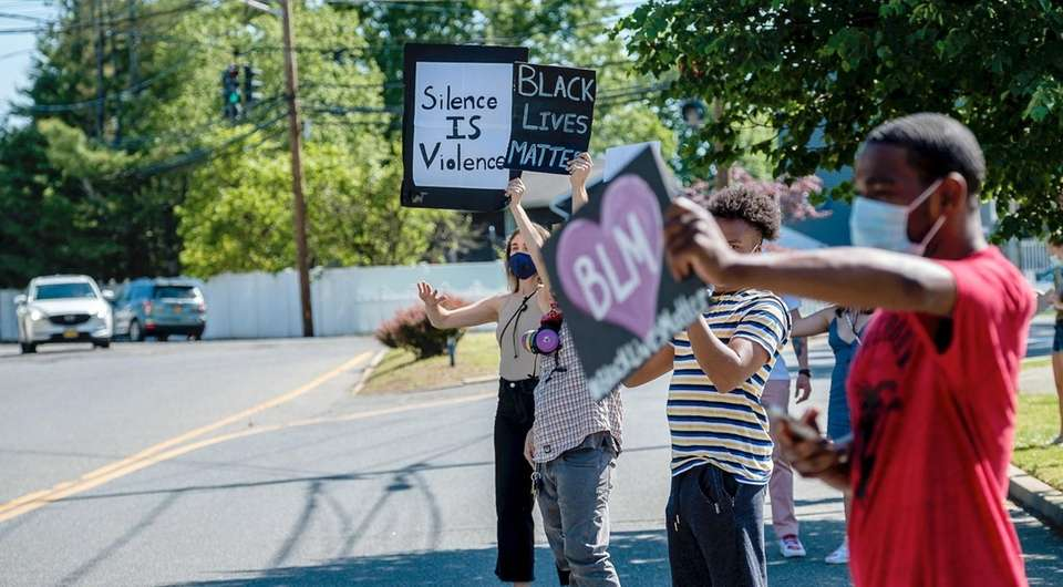 Demonstrators gather on Broadway in Massapequa to protest