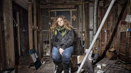 Amy Italiano sits in her gutted home in